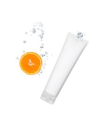 Splashing orange into a water with cosmetic tube photo