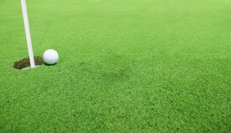 Golf ball near the hole photo