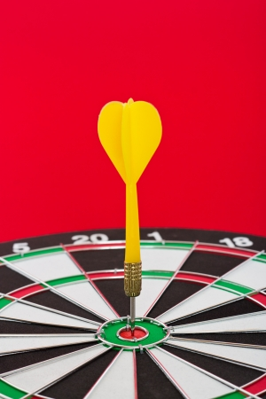 Dart sticks to bullseye on a dart board photo