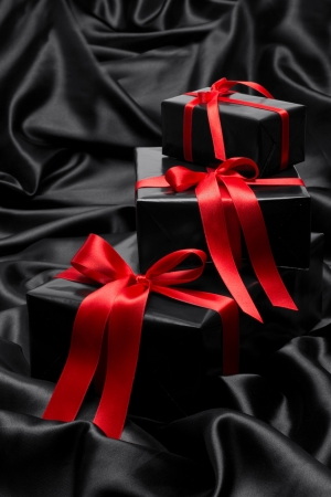 Black gift boxe with red satin ribbons and bows, over black satin photo