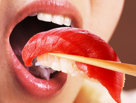 Beautiful young woman eating sushi Stock Photo - 21966449