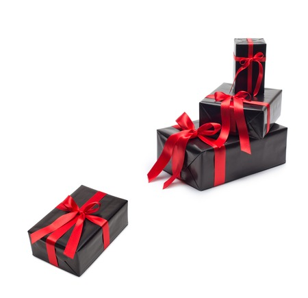 black satin: Black gift box with red satin ribbon and bow, over black satin Stock Photo