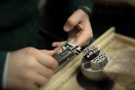 mesure: A jeweler mesure a emerald for setting into a emerald ring mount.