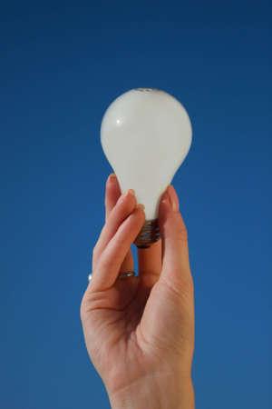 A hand holding a light bulb