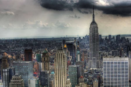 New york skyline with the Empire State building as the primary focus with dark clouds in the background and light beams coming down