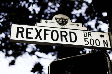 Rexford drive sign against a blue sky and silhouetted tree