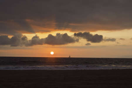 Sunset over the pacific with a sail boat on the horizon Banco de Imagens - 6298816
