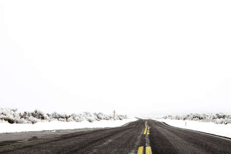 Road surrounded by snow with space for text on the white sky Stock Photo