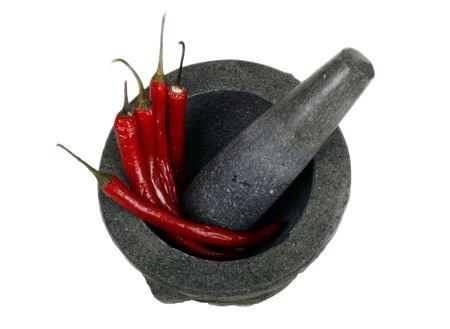 mortero: Granito y mortero de pestle con chiles rojos