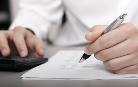 A businessman calculating expenses at tax time Stock Photo