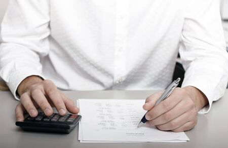 A businessman calculating expenses at tax time photo