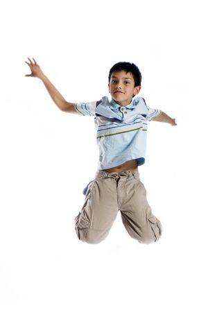 ni�o saltando: Muchacho joven que salta para arriba aislado en blanco