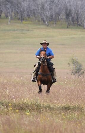 The man from Snowy Mountains riding a horse at full gallop photo