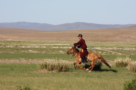 Mongolian horse herdsmen on horseback, riding full speed photo