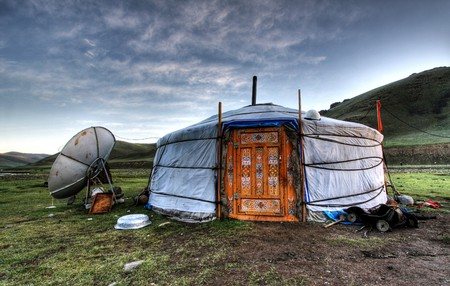 Mongolian dwelling on the green plain of grass photo