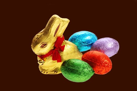 A golden chocolate Easter bunny with eggs isolated with area for text photo