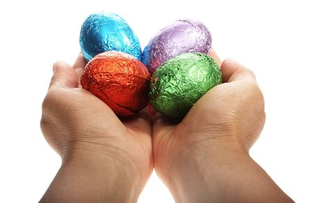 two hands holding chocolate Easter eggs isolated with area for text photo