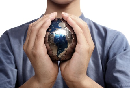 Earth puzzle, held by a young boy looking for solution photo