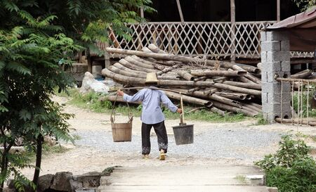 Old Chinese women carrying two buckets of water Stock Photo - 4570667