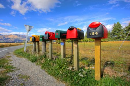 ship package: Colorful row of post boxes by a roadside Stock Photo