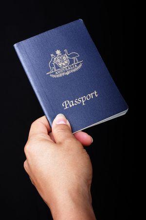 pasaportes: Pasaporte australiano sobre fondo negro Foto de archivo