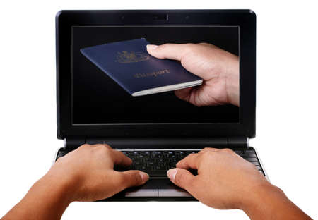 submitting: Female hands typing on a keyboard of a mini laptop, submitting a passport Stock Photo