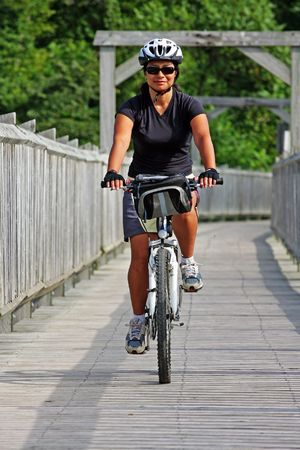 women rider crossing a bridge in Canada Stock Photo