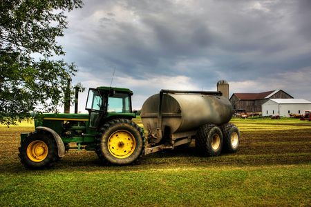 Tractor against a dramatic sky on a green field Stock Photo