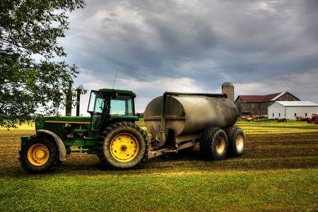 traktor: Traktor gegen einen dramatischen Himmel auf der gr�nen Wiese Lizenzfreie Bilder