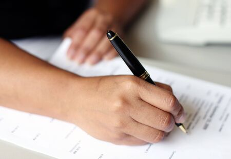 signing an important document with a black pen photo