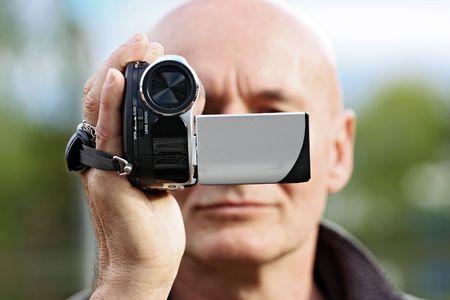 aficionado: camar�grafo aficionado con una peque�a videoc�mara digital Foto de archivo
