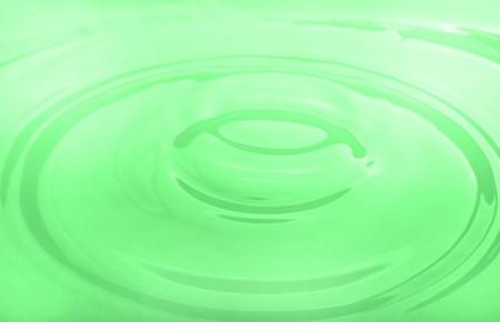 drop of green milk falling into a bowl photo
