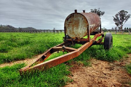 Rusty oil drum wagon on grass photo