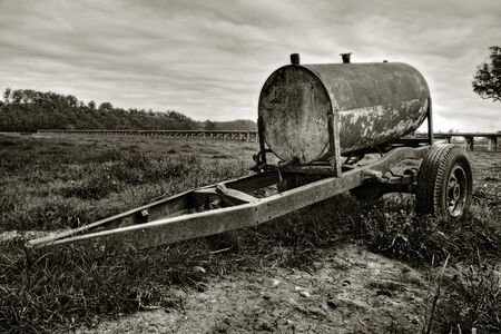 Rusty oil drum wagon on grass photo