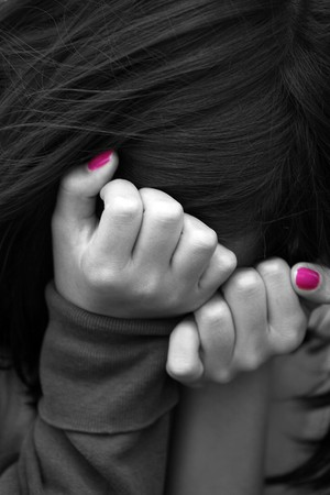 children sad: young girl hiding her face Stock Photo