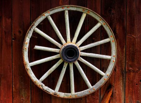 rustic wagon wheel hanging on a wall photo