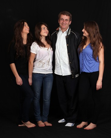 three happy sisters and dad against black background