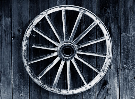 horse carriage: rustic wagon wheel hanging on a wall Stock Photo