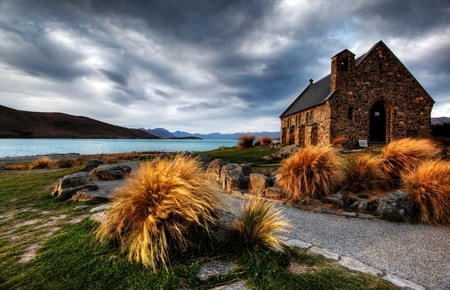 tekapo: quiet church by a glacier lake against a mountain backdrop Stock Photo