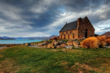 quiet church by a glacier lake against a mountain backdrop photo