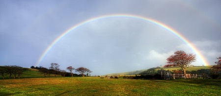 rainbow scene: rainbow over a farm field