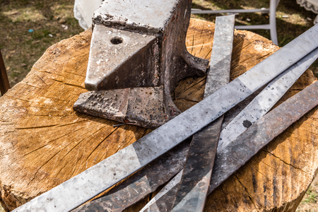 medieval blacksmith: Anvil and iron plates on a wooden table Stock Photo