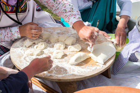 yufka: Preparation of a traditional Turkish yufka for pastries - gozleme by hands of a women.