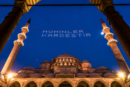 """ISTANBUL, TURKEY - JUNE 4, 2017:Mahya of """"Muslims are brother"""" is written and hung between minarets of Suleymaniye Mosque. Mahya is to write with light especially during ramadan month for muslims Editorial"""