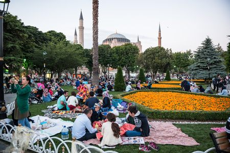 Muslim people who are fasting wait for the adhan (ezan) and evening meal (Iftar) in Ramadan month in Sultan Ahmet Park, Istanbul,Turkey.ISTANBUL,TURKEY,JUNE 11,2017