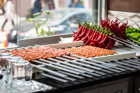 Several Adana Kebab skewers lined up waiting to be cooked and served.Raw Turkish Traditional Sish kebab, Meat, liver, beef, meat ready for cook at a restaurant.Green and red pepper skewered to be grilled on background.