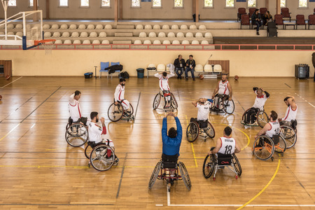 Unidentified disabled people doing exercise before playing game of wheelchair basketball at a basketball Show.TURKEY, ISTANBUL,21 JANUARY 2017