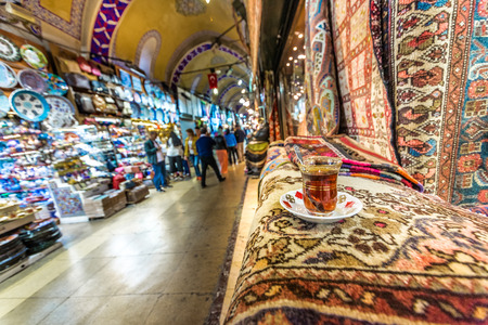 Unidentified people visiting the Grand Bazaar for shopping,Turkish tea on the foreground .Interior of the Grand Bazaar with souvenirs  in  Istanbul, Turkey.April 17, 2017