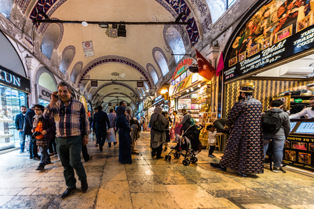 ISTANBUL, TURKEY- APRIL 17, 2017: Unidentified Tourists visiting and shopping in the Grand Bazaar in Istanbul. Interior of the Grand Bazaar with souvenirs on the foreground. Editorial