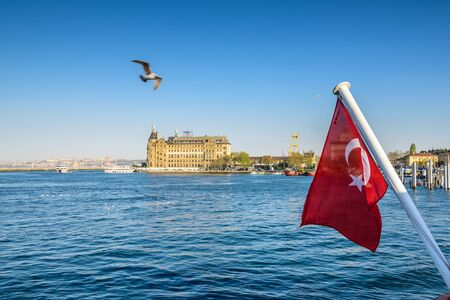 View of historical train terminal named Haydarpasa from Traditional public ferry Turkish flag on foreground.ISTANBUL,TURKEY,APRIL 20,2017